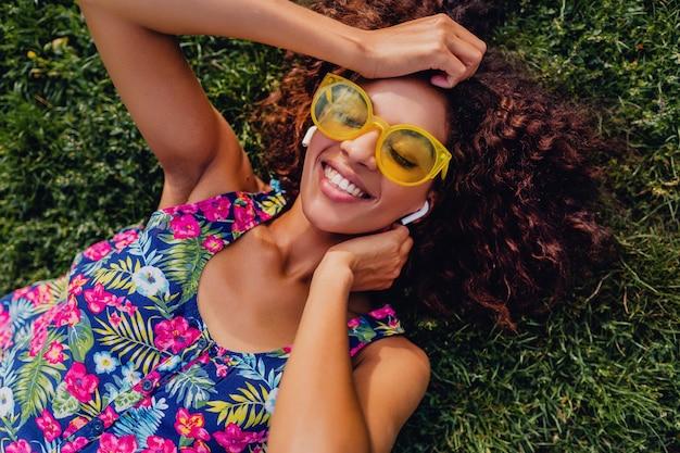 Jonge stijlvolle zwarte vrouw luisteren naar muziek op draadloze oortelefoons plezier liggend op gras in park, zomer fashion stijl, kleurrijke hipster outfit, van bovenaf bekijken