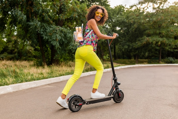 Jonge stijlvolle zwarte vrouw plezier in park rijden op elektrische kick scooter in zomer fashion stijl, kleurrijke hipster outfit, rugzak en gele broek en zonnebril dragen