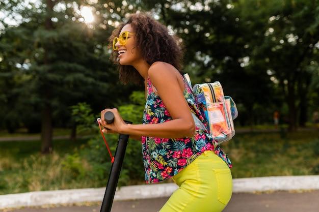 Jonge stijlvolle zwarte vrouw plezier in park rijden op elektrische kick scooter in zomer fashion stijl, kleurrijke hipster outfit, rugzak en gele zonnebril dragen