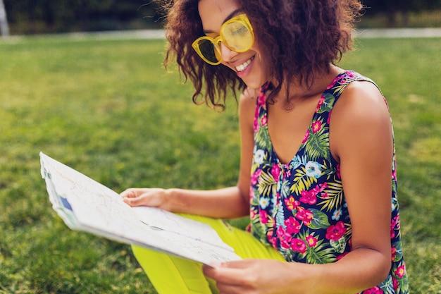 Jonge stijlvolle zwarte vrouw plezier in park zomer mode stijl, kleurrijke hipster outfit, zittend op het gras, reiziger met een kaart