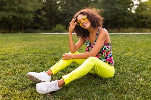 Jonge stijlvolle zwarte vrouw plezier in park zomer mode stijl, kleurrijke hipster outfit, zittend op het gras