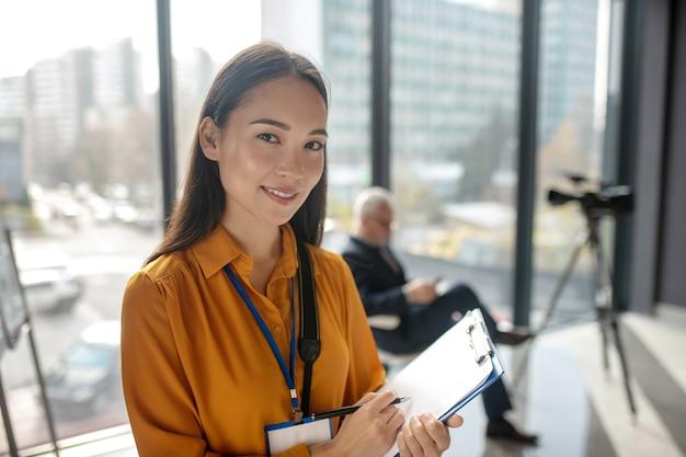 Jonge stralende mooie aziatische verslaggever kijkt tevreden tijdens het maken van aantekeningen