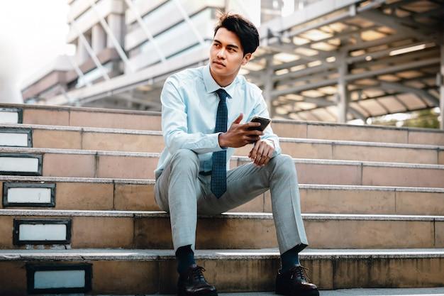 Jonge streven aziatische zakenman zittend op de trap in de stad. hand met een mobiele telefoon