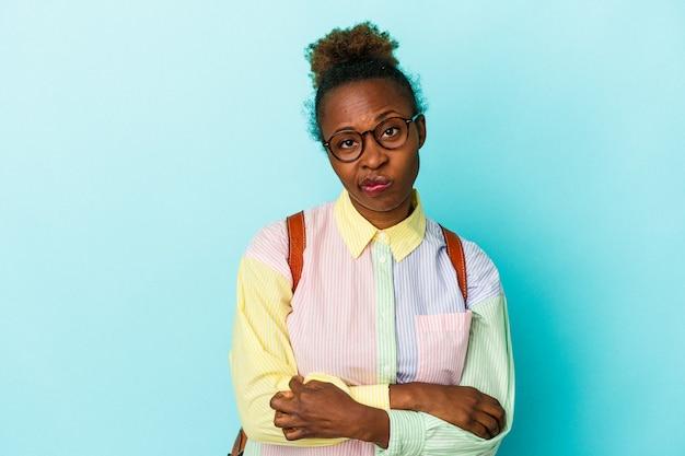 Jonge student afro-amerikaanse vrouw over geïsoleerde achtergrond ongelukkig in de camera kijken met sarcastische uitdrukking.