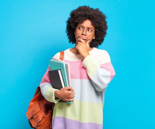 Jonge student afro vrouw denken, twijfelachtig en verward voelen, met verschillende opties, zich afvragend welke beslissing ze moet nemen