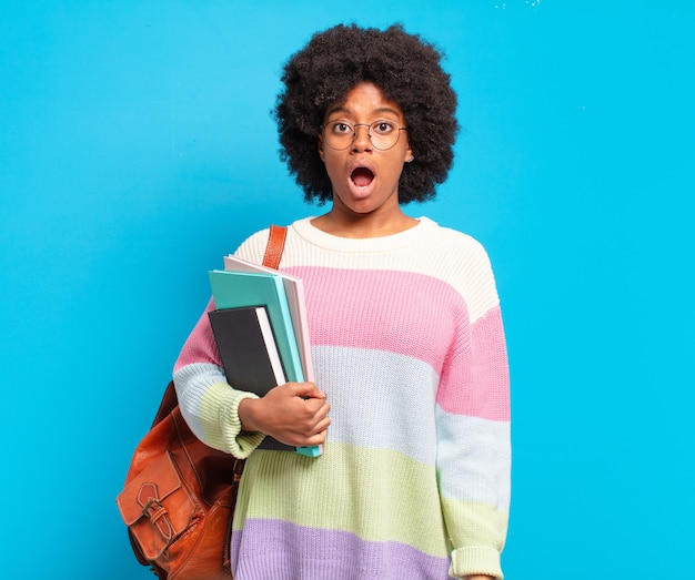 Jonge student afro-vrouw die erg geschokt of verrast kijkt, starend met open mond en zegt wow