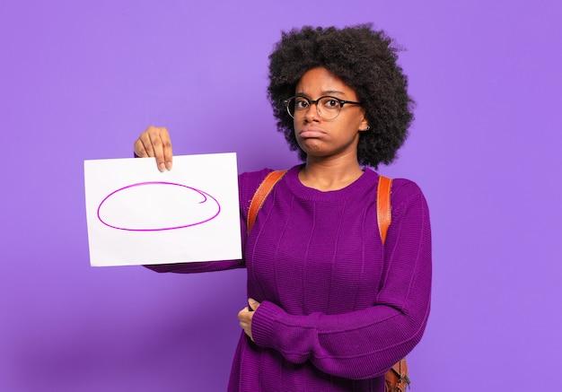 Jonge student afro-vrouw die haar schouders ophaalt, zich verward en onzeker voelt, twijfelt met gekruiste armen en een verbaasde blik