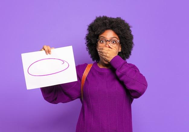 Jonge student afro-vrouw die mond bedekt met handen met een geschokte, verbaasde uitdrukking, een geheim houdt of oeps zegt