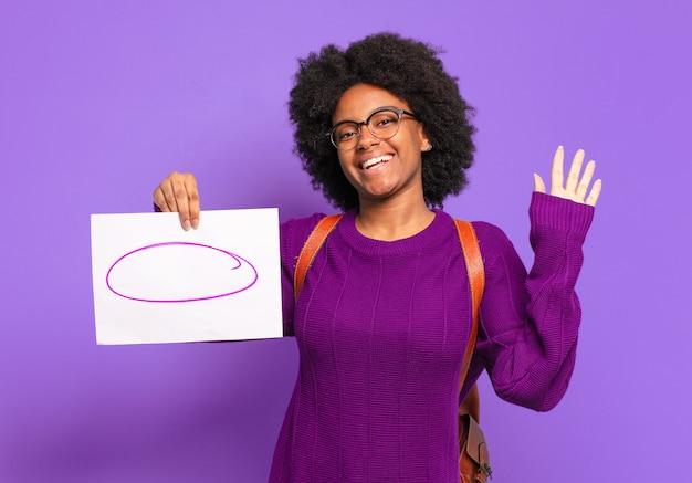 Jonge student afro-vrouw die vrolijk en opgewekt lacht, met de hand zwaait, je verwelkomt en begroet, of afscheid neemt