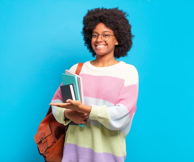 Jonge student afro-vrouw die vrolijk glimlacht, zich gelukkig voelt en een concept in exemplaarruimte met handpalm toont