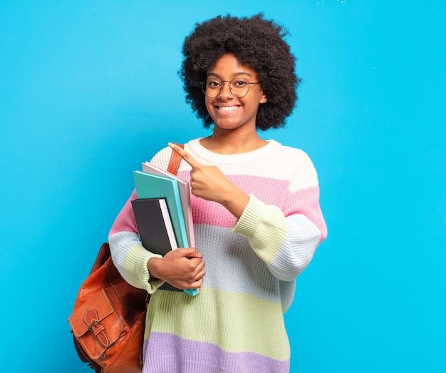 Jonge student afro-vrouw die vrolijk lacht, zich gelukkig voelt en naar de zijkant en naar boven wijst, een object in de kopieerruimte laat zien