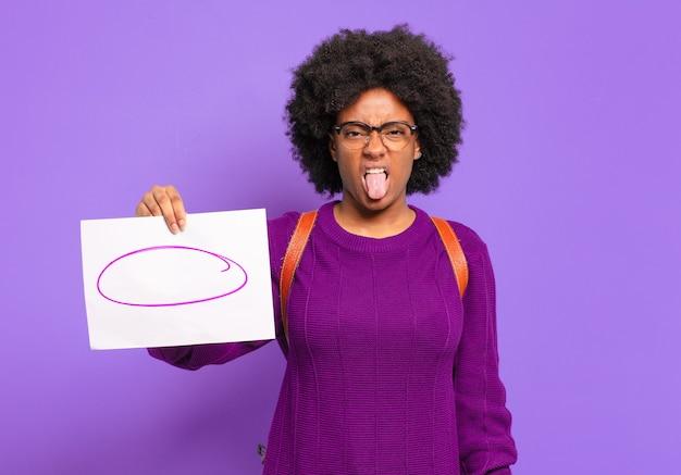 Jonge student afro-vrouw die walgt en geïrriteerd voelt, tong uitsteekt, een hekel heeft aan iets smerigs en vies