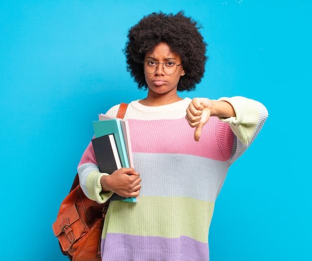 Jonge student afro-vrouw die zich boos, boos, geïrriteerd, teleurgesteld of ontevreden voelt, duimen naar beneden met een serieuze blik