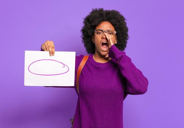 Jonge student afro-vrouw die zich gelukkig, opgewonden en positief voelt, een grote schreeuw geeft met handen naast de mond, roept