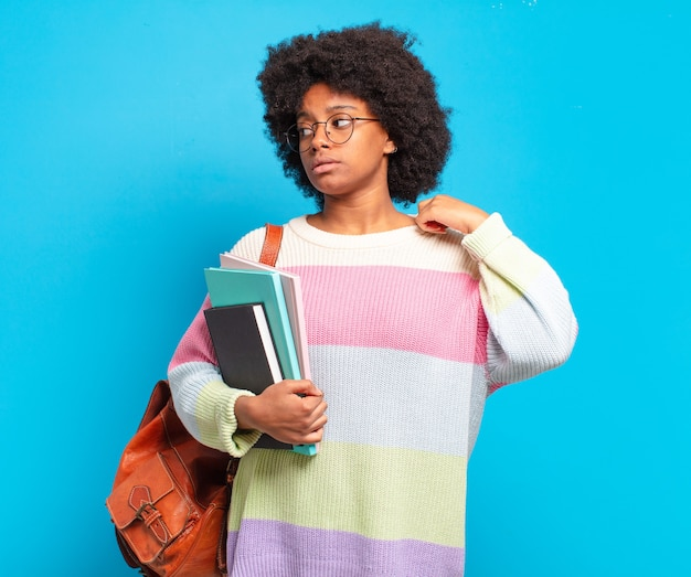 Jonge student afro-vrouw die zich gestrest, angstig, moe en gefrustreerd voelt, aan de hals van het shirt trekt, gefrustreerd kijkt door het probleem