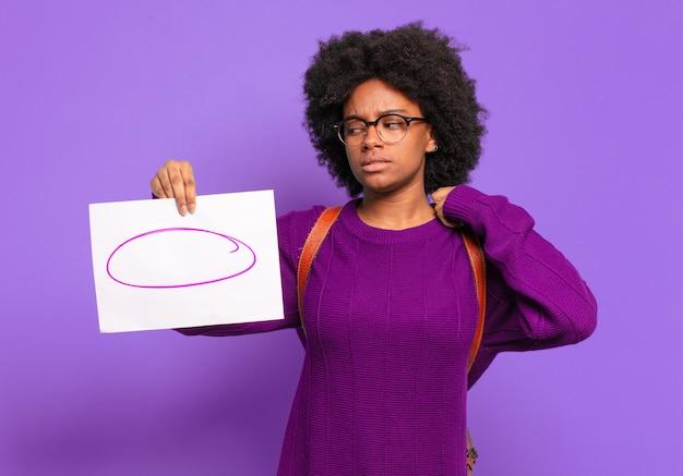 Jonge student afro-vrouw die zich gestrest, angstig, moe en gefrustreerd voelt, aan de nek van het shirt trekt, gefrustreerd kijkt met een probleem