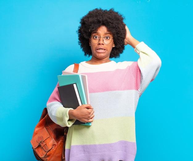 Jonge student afro-vrouw die zich gestrest, bezorgd, angstig of bang voelt, met de handen op het hoofd, in paniek raakt bij een fout
