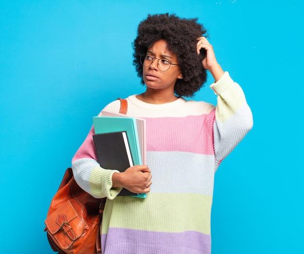 Jonge student afro-vrouw die zich verbaasd en verward voelt, hoofd krabt en opzij kijkt