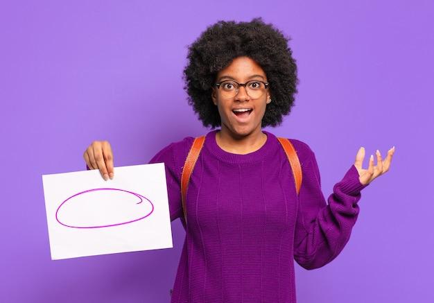 Jonge student afro-vrouw die zich verrast voelt met een vel papier met een schets