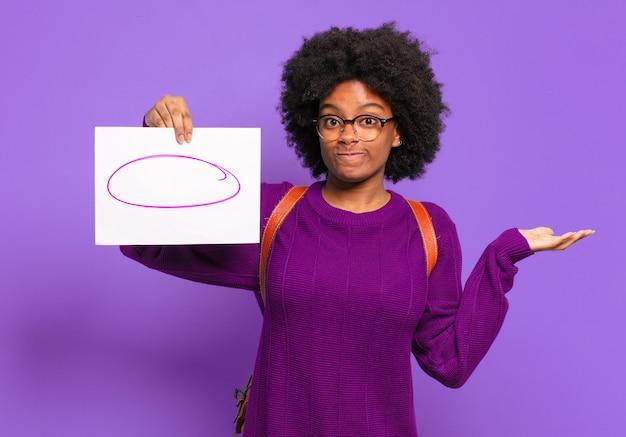 Jonge student afro-vrouw die zich verward en verward voelt, twijfelt, weegt of verschillende opties kiest met grappige uitdrukking