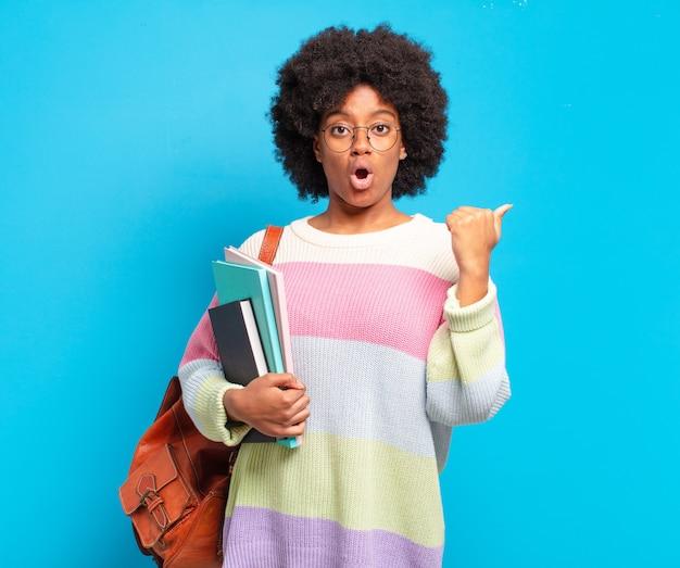Jonge student afro-vrouw kijkt verbaasd van ongeloof, wijst naar een voorwerp aan de zijkant en zegt wow, ongelooflijk