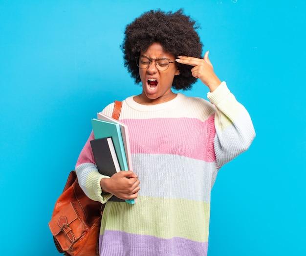 Jonge student afro vrouw op zoek ongelukkig en gestrest, zelfmoordgebaar pistool teken met hand, wijzend naar het hoofd