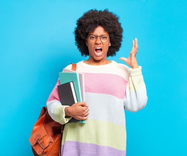 Jonge student afro-vrouw schreeuwend met handen in de lucht, woedend, gefrustreerd, gestrest en overstuur and