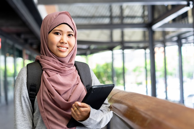 Jonge student aziatische moslimvrouw glimlachend en houd tablet aan de universiteit voor onderwijsconcept