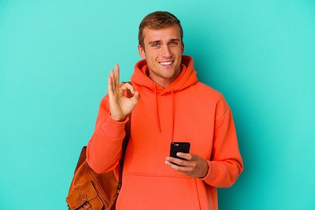 Jonge student blanke man met een mobiele telefoon geïsoleerd op blauwe muur vrolijk en zelfverzekerd tonend ok gebaar.