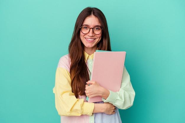 Jonge student blanke vrouw geïsoleerd op blauwe achtergrond gelukkig, lachend en vrolijk.