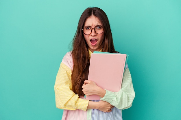 Jonge student blanke vrouw geïsoleerd op blauwe achtergrond schreeuwen erg boos en agressief. Premium Foto