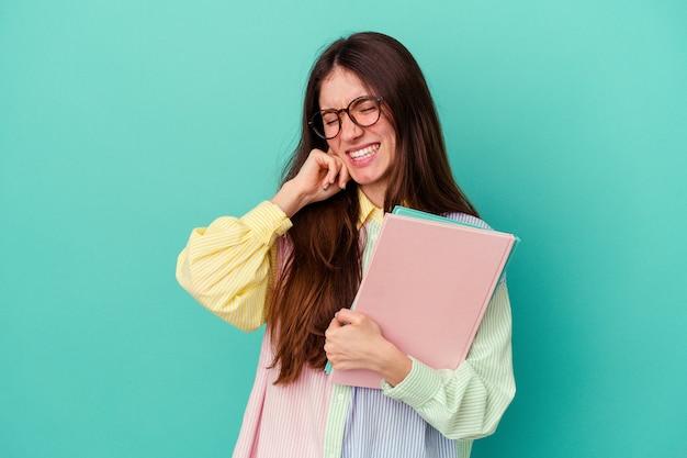 Jonge student blanke vrouw geïsoleerd op een blauwe achtergrond die oren bedekt met handen.