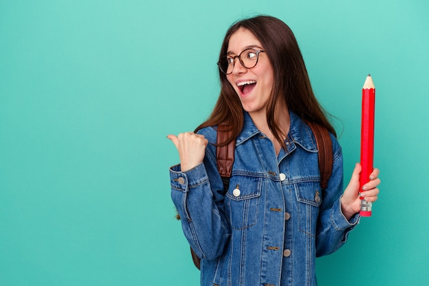 Jonge student blanke vrouw met een groot potlood geïsoleerd op blauwe achtergrond wijst met duimvinger weg, lachend en zorgeloos.