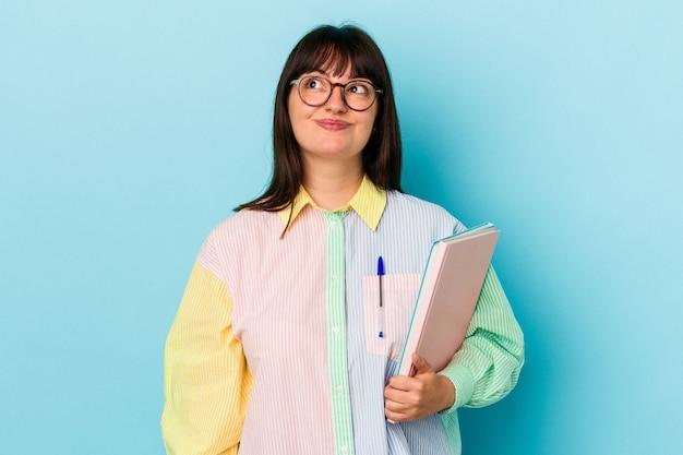 Jonge student bochtige vrouw met boeken geïsoleerd op blauwe achtergrond dromen van het bereiken van doelen en doeleinden