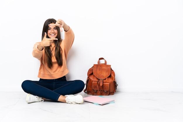 Jonge student braziliaanse vrouw zittend op de vloer gericht gezicht. frame symbool