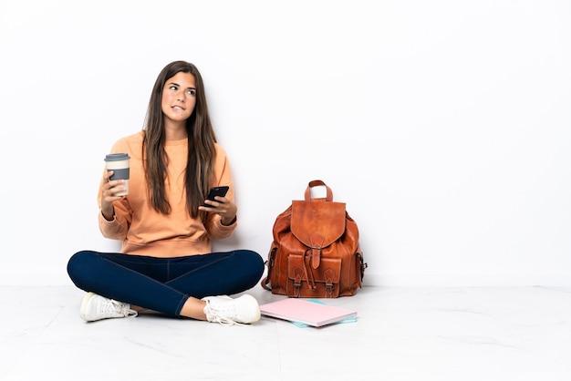 Jonge student braziliaanse vrouw zittend op de vloer koffie te houden om mee te nemen en een mobiel terwijl je iets denkt