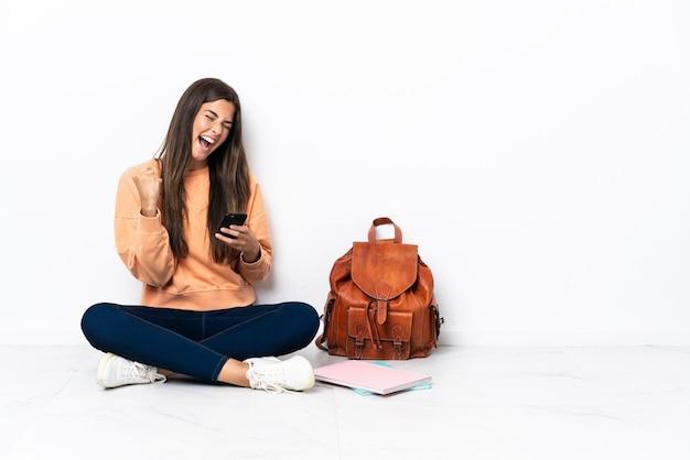 Jonge student braziliaanse vrouw zittend op de vloer met telefoon in overwinningspositie