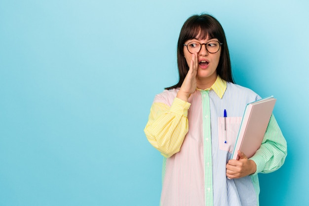 Jonge student curvy vrouw met boeken geïsoleerd op blauwe achtergrond zegt een geheim heet remnieuws en kijkt opzij