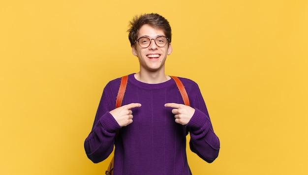 Jonge student die blij verrast en trots naar zichzelf wijst met een opgewonden verbaasde blik