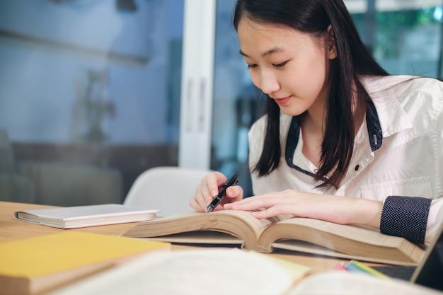 Jonge student die een boek leest.