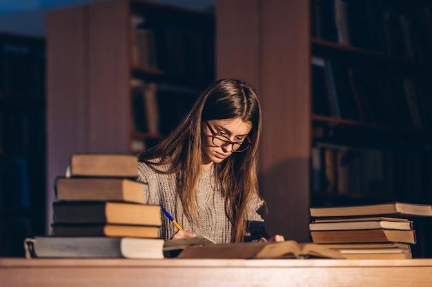 Jonge student die in glazen het examen voorbereidt. het meisje zit 's avonds aan een tafel in de bibliotheek met een stapel boeken
