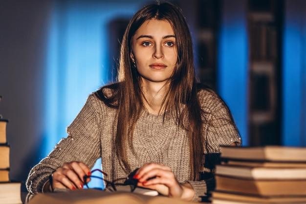 Jonge student die in glazen voor het examen voorbereidingen treft. meisje in de avond zit aan een tafel in de bibliotheek met een stapel boeken