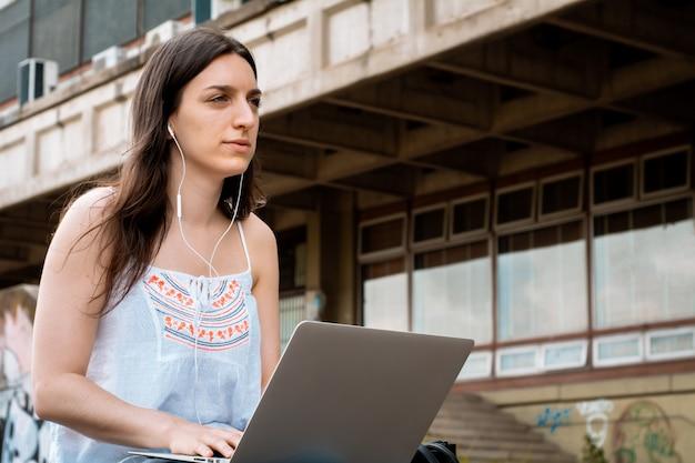 Jonge student die laptop in openlucht met behulp van.