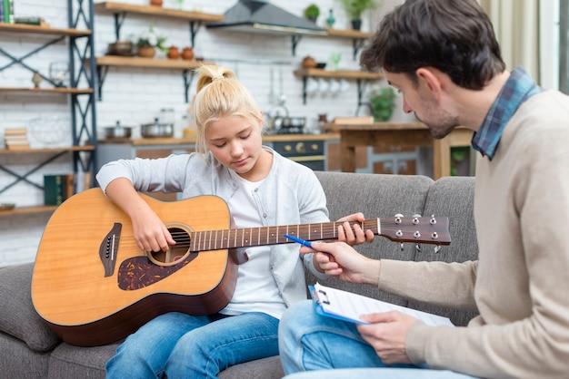 Jonge student die leert hoe de gitaar te houden