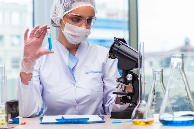 Jonge student die met chemische oplossingen in laboratorium werkt