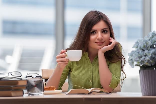 Jonge student die voor examens voorbereidingen treft die thee drinken