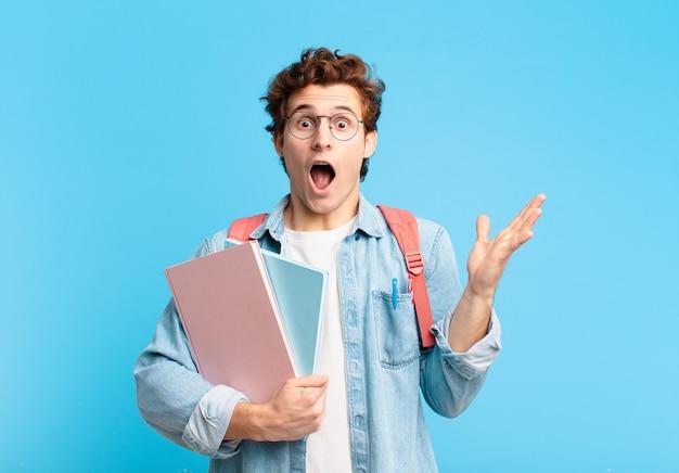 Jonge student die zich gelukkig, opgewonden, verrast of geschokt voelt, glimlacht en verbaasd over iets ongelooflijks