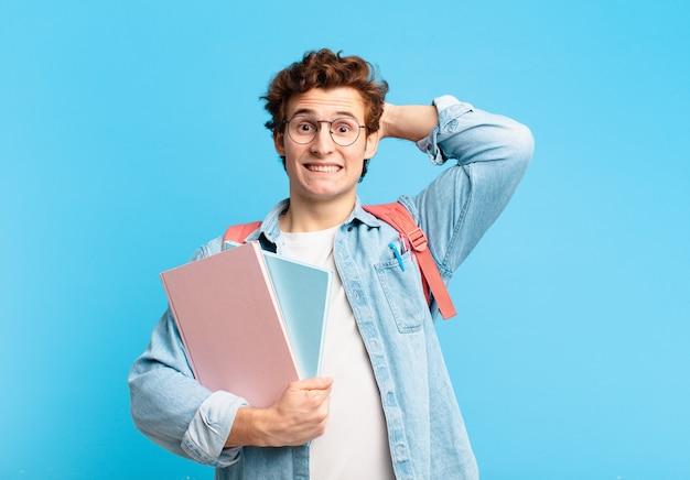 Jonge student die zich gestrest, bezorgd, angstig of bang voelt, met de handen op het hoofd, in paniek bij vergissing