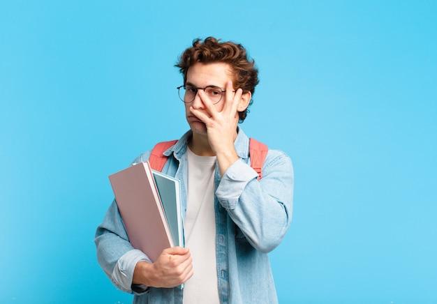 Jonge student die zich verveeld, gefrustreerd en slaperig voelt na een vermoeiende, saaie en vervelende taak, gezicht met de hand vasthoudend