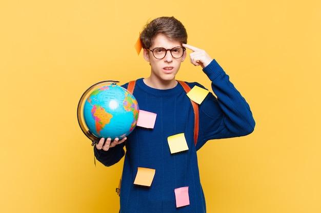 Jonge student die zich verward en verbaasd voelt en laat zien dat je gek, gek of gek bent